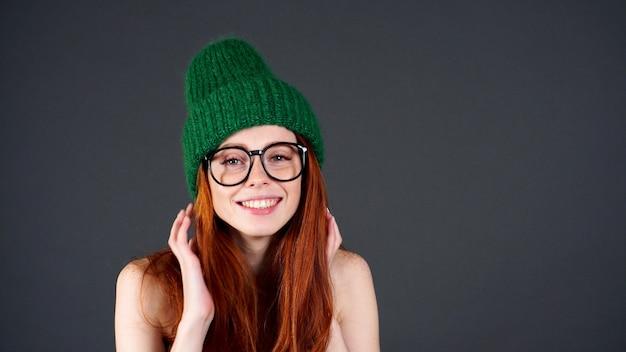 Счастливая красивая молодая женщина с рыжими длинными волосами, белыми зубами смотрит в камеру на изолированном сером фоне