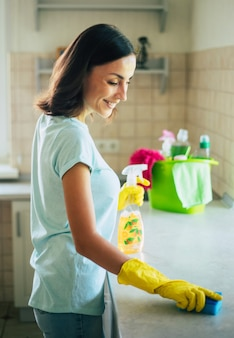 Happy beautiful young woman in yellow gloves is cleaning the kitchen with special equipment and spray