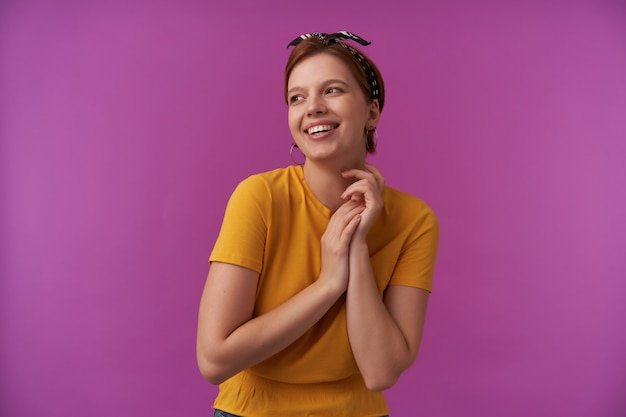 Happy beautiful young woman in yellow tshirt with headband on head smiling and looking away to the side at copyspace over purple wall