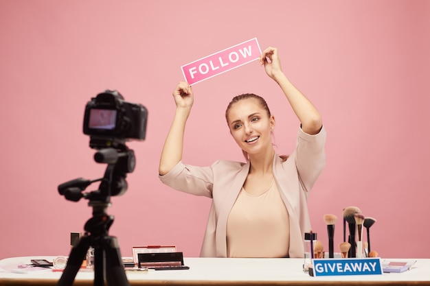 Happy beauty blogger talking to her followers online and says to follow of her blog