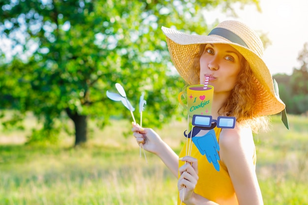 Happy beauty comic woman female wears yellow summer lite dress and summer hat enjoying sunny day outdoor in green park with colorful party props. active funny outdoor leisure lifestyle concept.