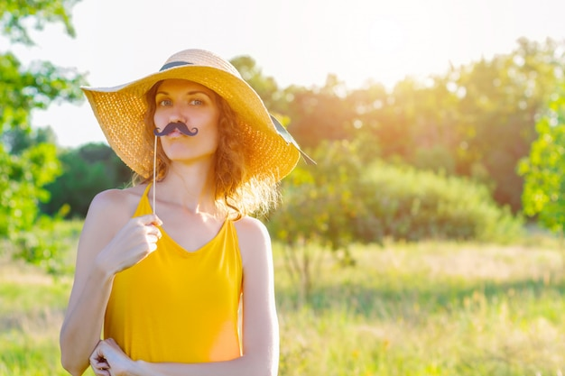 Happy beauty comic woman female wears yellow summer lite dress and summer hat enjoying sunny day outdoor in green park with mustache props. active funny outdoor leisure lifestyle concept.