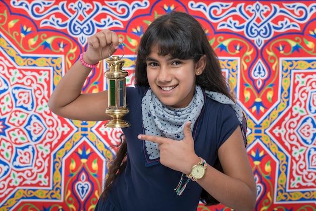 Счастливая девушка красоты с фонарем празднует рамадан