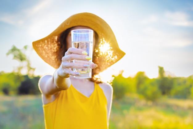 純粋な水のガラスを持つ幸せな美しさ若い女性女性は黄色のライトドレスと晴れた暖かい光の日に緑豊かな公園で屋外を歩いて笑っている夏の帽子を着ています。アクティブなアウトドアライフスタイルレジャーコンセプト。