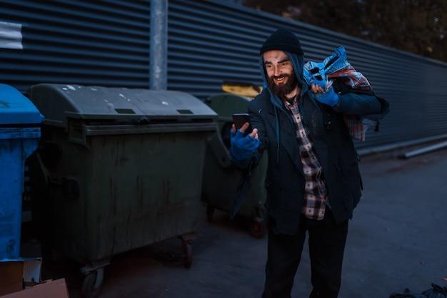 幸せな乞食は、街の通りのゴミ箱で携帯電話を見つけました。