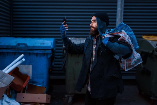 幸せな乞食がゴミ箱に携帯電話を見つけた