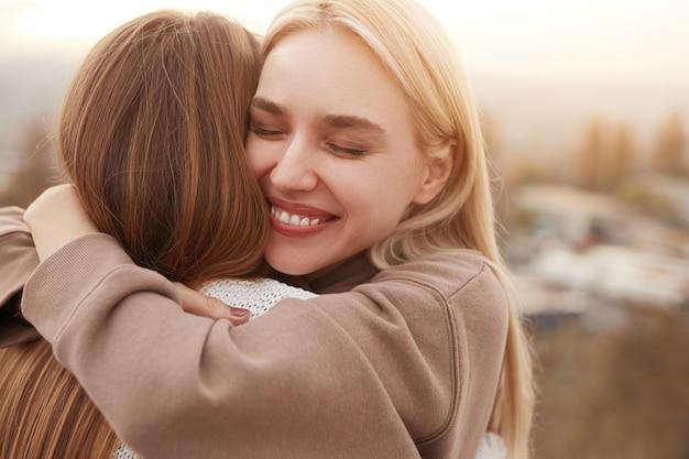 Happy best girlfriends hugging in nature