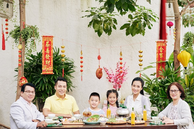 Happy big asian family sitting at big dinner table outdoors and celebrating lunar new year, decorations with best wishes inscription in background