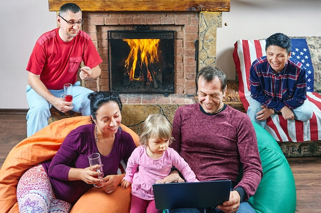 행복한 대가족은 성숙한 부부로 구성되어 있으며 어린 소녀는 함께 저녁을 보내고 있습니다.