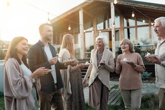 ケーキを食べて、新鮮な空気の上に立って笑って幸せな大家族 Premium写真