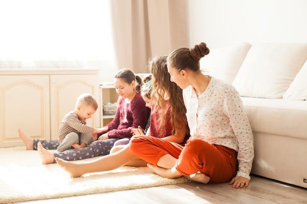 Счастливая большая семья братьев и сестер, сидя на полу