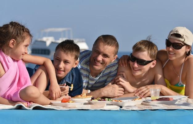 Счастливая большая семья на пикнике на пляже