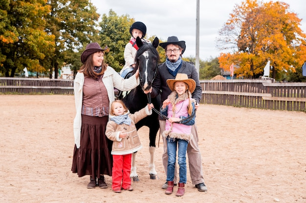 Happy big family spending time together on a horse farm