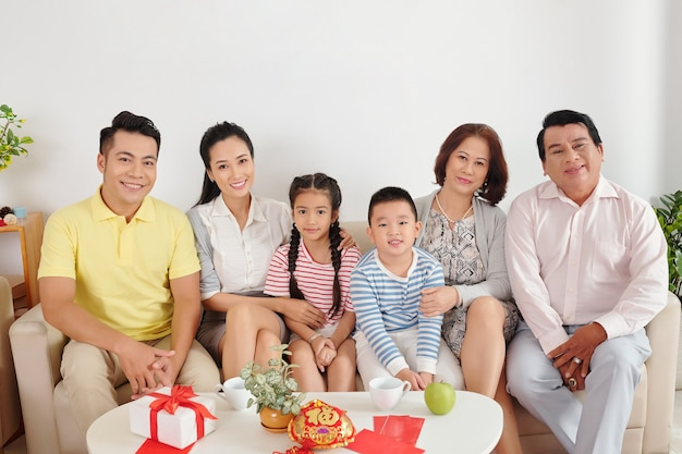 Happy big vietnamese family sitting on sofa in living room when celebrating lunar new year at home