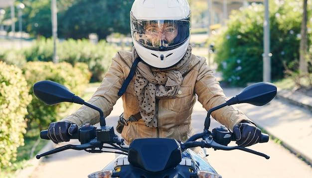 街の通りで彼女のバイクと幸せなバイカーの女性