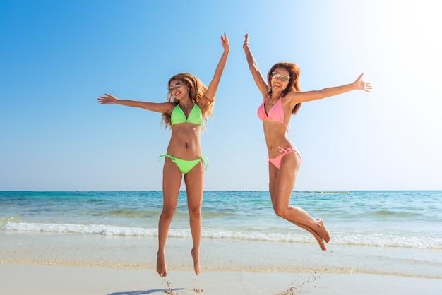 幸せなビキニ2アジアの女性は、カリブ海の熱帯の休暇に完璧な白い砂浜で喜びと成功のジャンプ。セクシーなスリムな日焼けの体の自由と幸福の実行と休日の女の子。