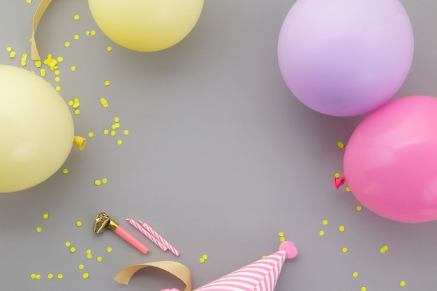 Happy birthday background, flat lay colorful party decoration on pastel grey background.