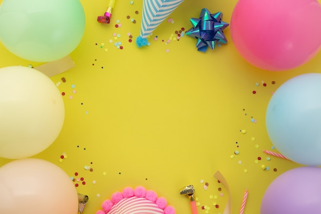 Happy birthday background, flat lay colorful party decoration on pastel yellow background.