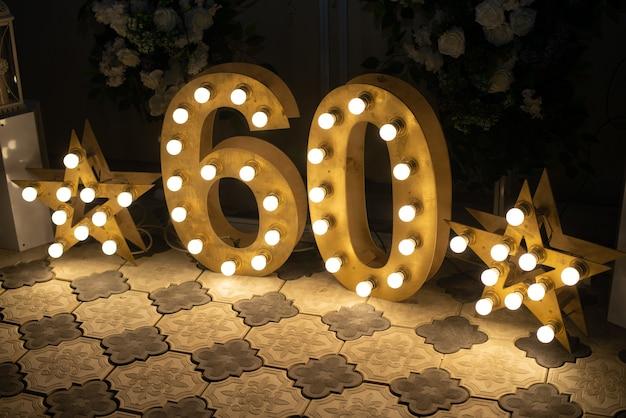 С днем рожденья! дневное украшение интерьера на шестьдесят лет. звездные огни. числа 60 вырезаны из дерева с подсветкой.