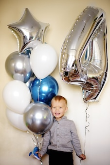 Happy birthday boy with balloons at home