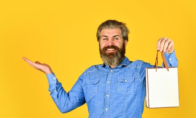 お誕生日おめでとう。ギフトを購入します。ブラックフライデー。小売コンセプト。流行に敏感な購入セール価格。サイバーマンデーセール。素敵な購入。あごひげを生やした男は買い物袋を持っています。ハンサムなバイヤー。季節限定セール。特別なオファー。