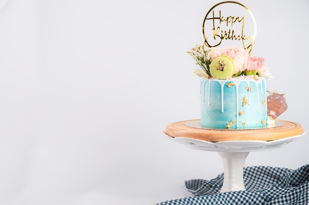 Happy birthday cake with macaroons and flowers on stand