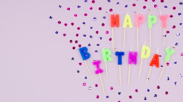 Happy birthday candles and confetti on purple background
