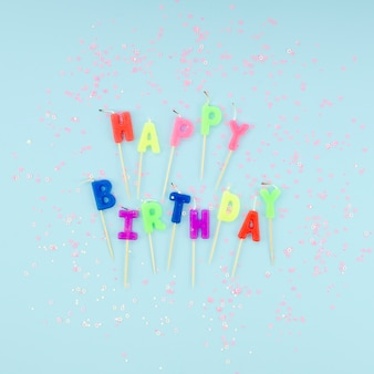 Happy birthday candles and glitter on blue background