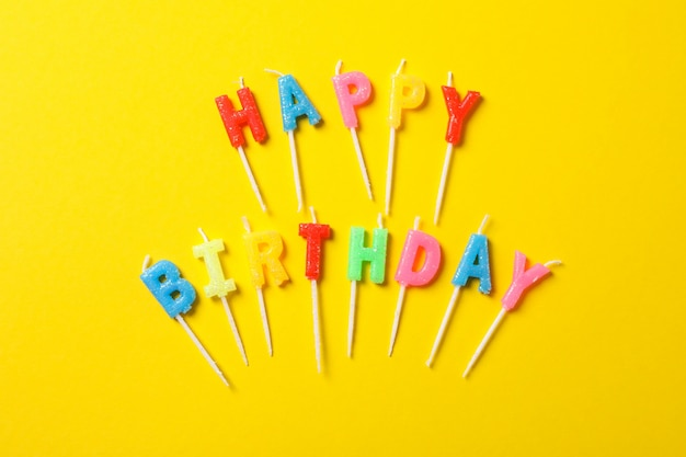 Happy birthday candles on yellow background. bright color wallpaper