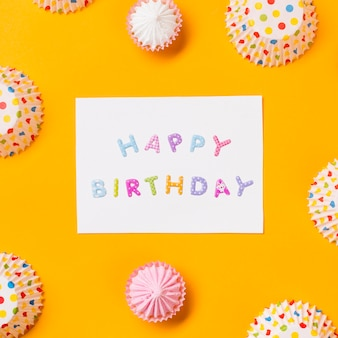 Happy birthday card decorated with aalaw and polka dots paper cake forms on yellow background