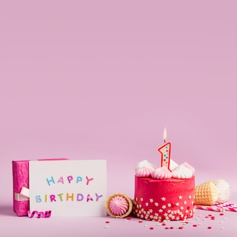 Happy birthday card near the cake with lighted candles and gift box on purple backdrop