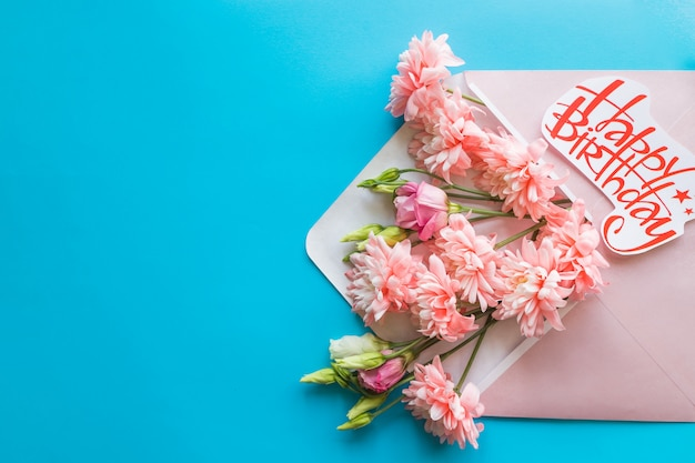 Happy birthday card. opened craft paper envelope filled with spring blossom flowers.