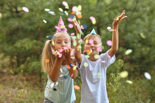屋外のbithdayパーティーで紙吹雪とお誕生日おめでとう子供たち
