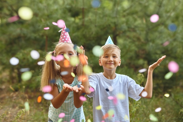 Happy birthday children with confetti on outdoor bithday party