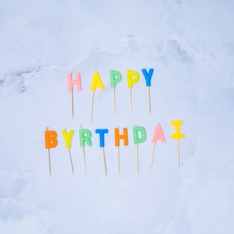 Happy birthday colorful candles on marble background