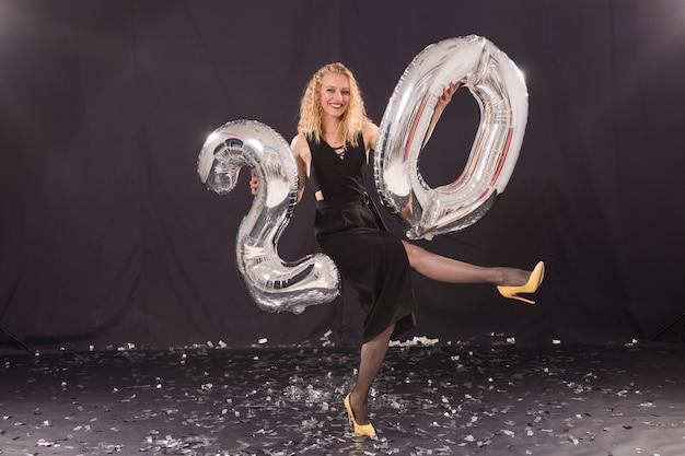 생일 축하 개념 - 숫자 모양의 20개의 풍선을 가진 아름다운 젊은 여성.