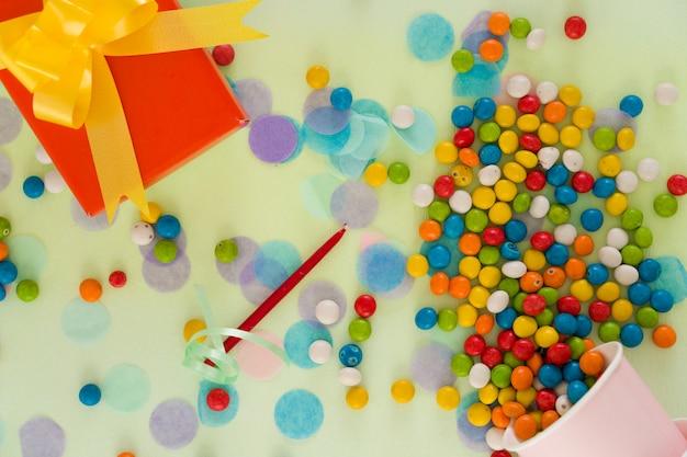 Концепция с днем рождения. подарочная коробка, шоколадные конфеты и предметы для вечеринок разбросаны по столу. вид сверху