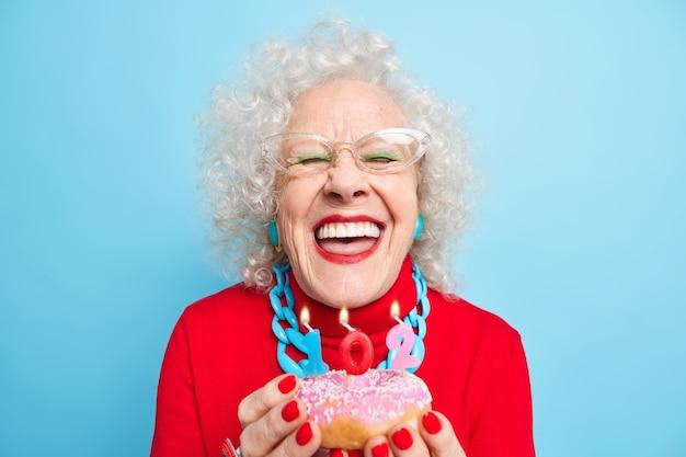 생일 축하 해요. 기뻐하는 노인 여성의 미소는 넓게 하얀 완벽한 이빨을 가지고 있으며 잘 차려 입은 유약을 바른 도넛에 촛불을 불어 넣을 것입니다.