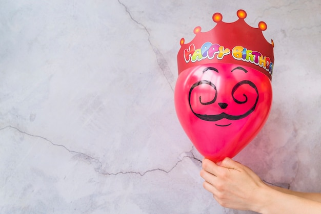 Happy birthday crown on pink balloon against cracked wall