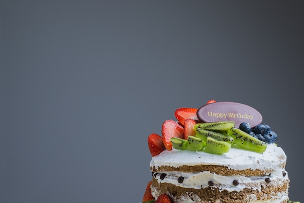 Happy birthday fresh fruit cake with chocolate happy birthday on cake concept with strawberry kiwi fruit cake. food