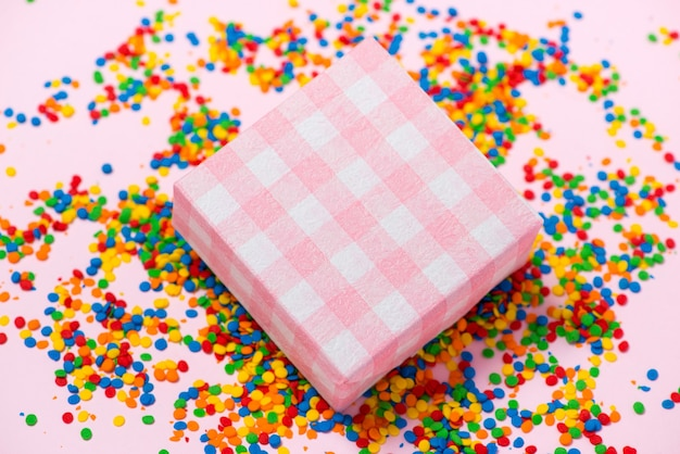 Happy birthday and gift box on candies background