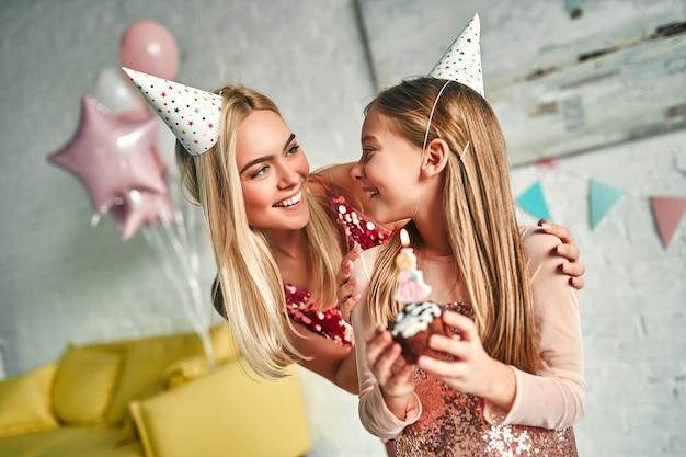 생일 축하해! 생일 케이크에 촛불을 끄는 소녀, 예쁜 엄마, 사랑스러운 귀여운 딸은 비슷한 축제 드레스와 생일 모자를 쓰고 있습니다. 가족의 사랑스러운 순간.