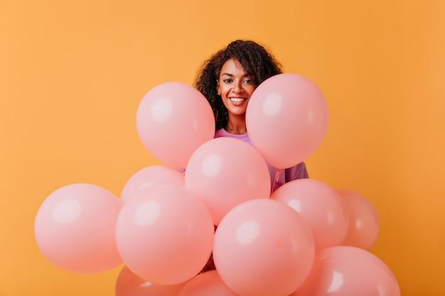 陽気な笑顔でポーズをとるお誕生日おめでとう女の子。オレンジ色に分離されたパーティー風船ときれいなアフリカの女性の屋内の肖像画。