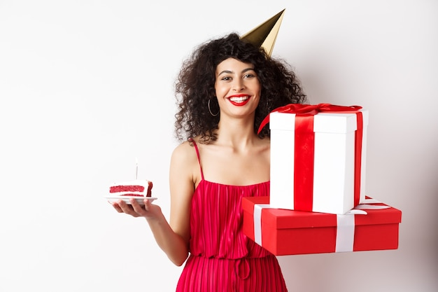 Happy birthday girl in red dress, celebrating and holding gifts with bday cake, standing on white background.