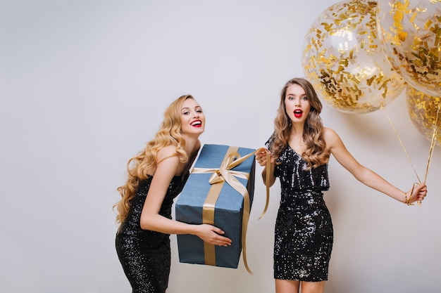 Happy birthday great party time of two charming funny young women. black luxury dresses, elegant outlook, long curly hair, having fun, present, balloons, expressing positivity.