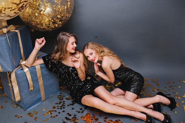Buon compleanno grande tempo di festa di due affascinanti giovani donne divertenti rilassarsi sul pavimento. abiti di lusso neri, aspetto elegante, lunghi capelli ricci, divertimento, presente, palloncini, orpelli.