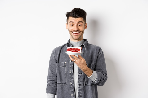 お誕生日おめでとう男は、b-dayケーキに願い事をし、笑顔で、白い背景の上に立って、興奮して点灯しているキャンドルを見てください。