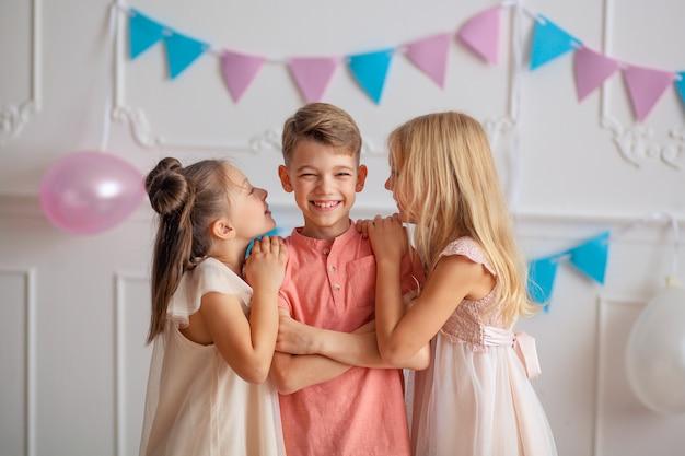 お誕生日おめでとうお祭りの装飾と美しいドレスを着たかわいい子供たちは、紙吹雪で遊んでいます。