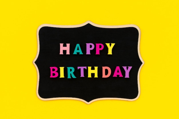 Happy birthday inscription from colorful letters on wooden board.