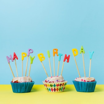 Happy birthday lettering on cupcakes